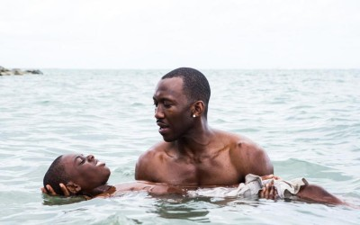 """This image released by A24 Films shows Alex Hibbert, left, and Mahershala Ali in a scene from the film, """"Moonlight.""""  The film is  a poetic coming-of-age tale told across three chapters about a young gay black kid growing up in a poor, drug-ridden neighborhood of Miami. (David Bornfriend/A24 via AP)"""