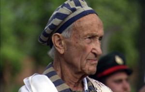 Ed Mosberg wearing the Tallit in Birkenau whilst listening to the Hatikva