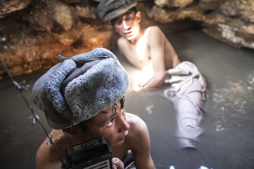 The Land of the Enlightened. Afghan boys listening to a radio